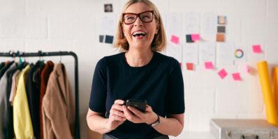Mulher feliz com celular na mão conhecendo os modelos de marcas