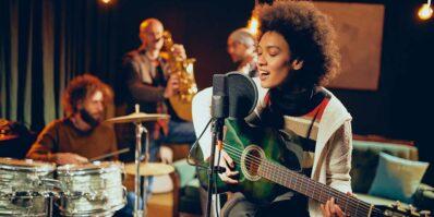 Mulher cantando e tocando violão - Como registrar nome artístico